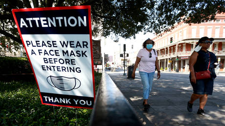 FILE PHOTO. Visitors walk past face mask signs along Decatur Street in the French Quarter in New Orleans, Louisiana. © Getty Images / Sean Gardner