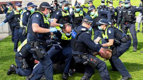 FILE PHOTO. Police tackle protesters in Melbourne during an anti-lockdown rally. © AFP / William WEST