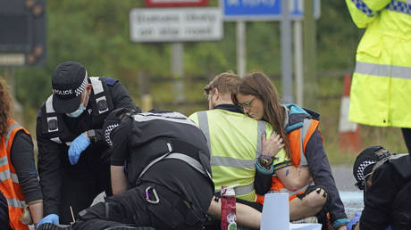 Police officers work to free protesters from Insulate Britain who glued themselves to the highway © PA via AP / Steve Parsons