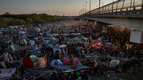 FILE PHOTO. Migrants take shelter along the Del Rio International Bridge, Texas, U.S. September 19, 2021. © Reuters / Adrees Latif