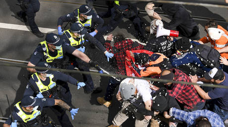 Victoria police fire pepper spray during a clash with protesters at a Rally for Freedom in Melbourne, Australia, Saturday, Sept. 18, 2021. © AAP Image via AP/James Ross