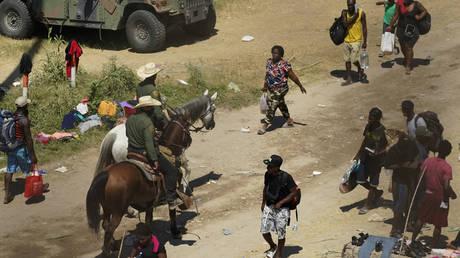 Border Patrol agents pass Haitian migrants at a makeshift camp in Del Rio, Texas, September 17, 2021 © AP / Eric Gay