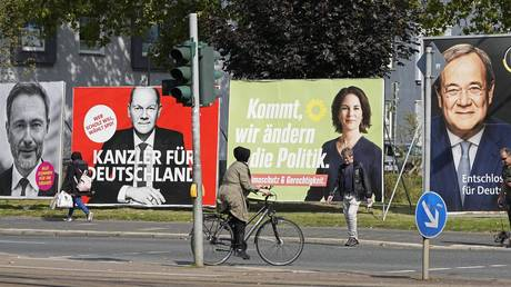 People walk and drive past election posters at a street in Gelsenkirchen, Germany on September 23, 2021.