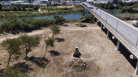 A bulldozer clears the makeshift camp set up by migrants under the Del Rio International Bridge on the US-Mexico border, September 24, 2021.