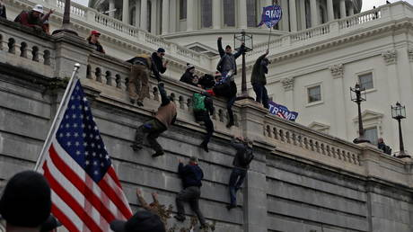 FILE PHOTO: People believed to be supporters of Donald Trump climb a wall during the January 6 riot. © REUTERS / Jim Urquhart