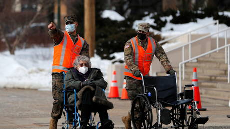 National Guard soldiers take elderly resident to receive Covid-19 vaccine shot at Westchester County Center in White Plains, New York