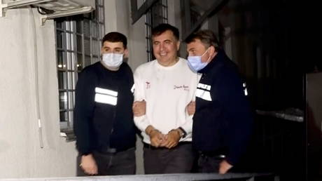 Georgia's former President Mikhail Saakashvili is escorted by police officers as he arrives at a prison in Rustavi, Georgia on October 1, 2021.