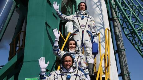 Roscosmos cosmonaut Anton Shkaplerov, actress Yulia Peresild, and film director Klim Shipenko of the ISS Expedition 66 prime crew pose by a Soyuz-2.1a rocket booster at the Baikonur Cosmodrome, in Baikonur, Kazakhstan. © Sputnik / Sergei Savostyanov
