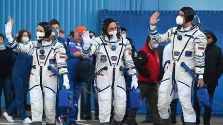 Roscosmos cosmonaut Anton Shkaplerov, actress Yulia Peresild, and film director Klim Shipenko of the ISS Expedition 66 prime crew pose by a Soyuz-2.1a rocket booster at the Baikonur Cosmodrome, in Baikonur, Kazakhstan. © Sputnik / Ramil Sitdikov