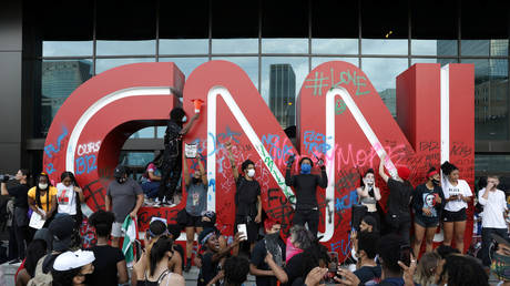 Protesters are shown in front of a damaged CNN sign at the media outlet's Atlanta headquarters during a demonstration in May 2020.