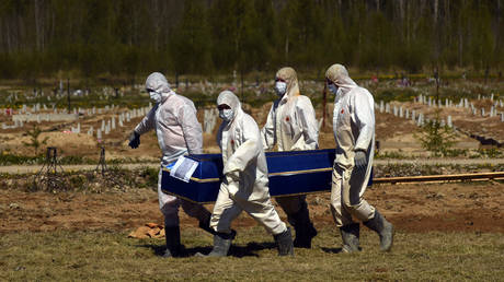 Cemetary employees in chemical protective suits carrying a coffin at the funeral of COVID-19 victims in Kolpino, outside St. Petersburg, Russia on May 23, 2020. © Sergey Nikolaev / NurPhoto via Getty Images