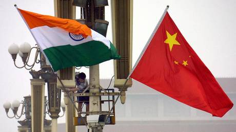Workers put up the Indian flag (L) alongside the Chinese flag on Tiananmen Square in Beijing, 22 June 2003. © AFP