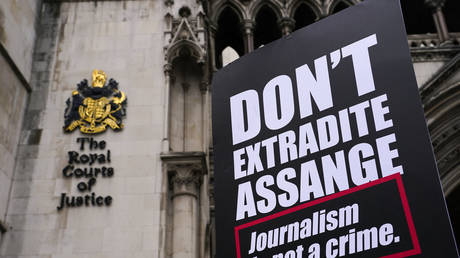 Placard in support of WikiLeaks founder Julian Assange is held outside the Royal Courts of Justice in London, Oct. 23, 2021