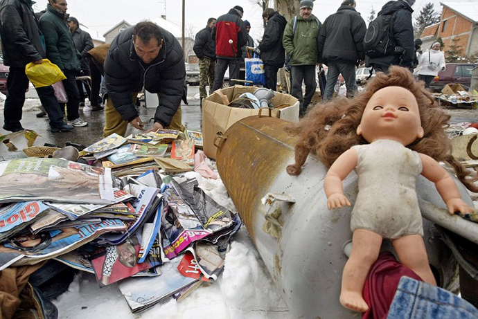 A man searches through magazines displayed for sale among other used things at a market in Belgrade. (AFP Photo / Koca Sulejmanovic)