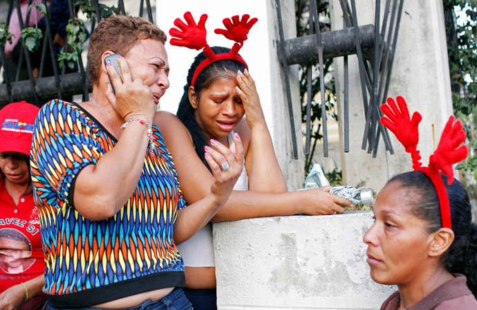 Supporters of Venezuela's President Hugo Chavez react to the announcement of his death outside the hospital where he was being treated in Caracas, March 5, 2013 (Reuters / Carlos Garcia Rawlins)