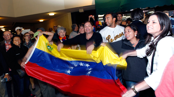 A crowd sings and waves the Venezuelan flag at a local restaurant following the death of Venezuelan President Hugo Chavez, in Doral, Florida, March 5, 2013 (Reuters / Robert Sullivan)