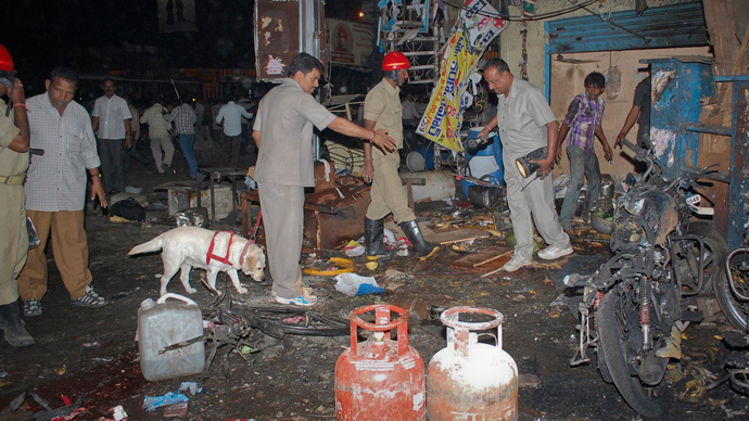 Investigating officers use a sniffer dog as they inspect the site of an explosion at Dilsukh Nagar, in the southern Indian city of Hyderabad February 21, 2013 (Reuters / Stringer)