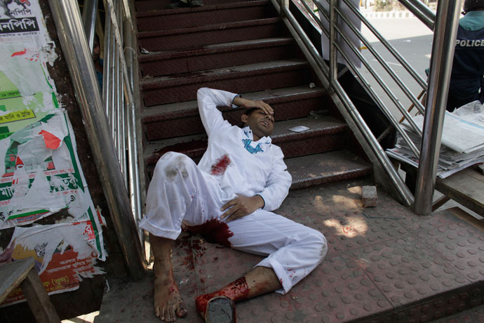 An activist, from one of the 12 Islamist parties involved in a clash, lies by an overhead bridge after being injured by a rubber bullet shot by the police in Dhaka February 22, 2013.(Reuters / Andrew Biraj)