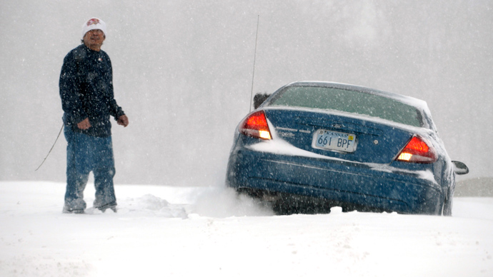 A man stands next to his car that is stuck in the snow during a blizzard in Kansas City, Kansas, February 21, 2013 (REUTERS / Dave Kaup)