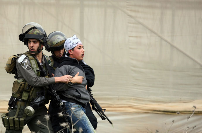 Israeli border police detain a Palestinian demonstrator following clashes at the entrance of the Jalama checkpoint, near the West Bank city of Jenin, on February 22, 2013.(AFP Photo / Saif Dahlah)