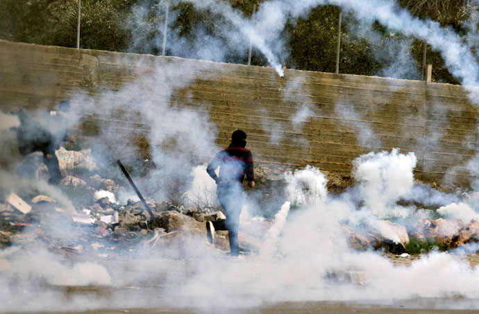 Palestinian protestors run for cover from tear gas fired by Israeli security forces during clashes next to Ofer prison, near the West Bank city of Ramallah, on February 22, 2013.(AFP Photo / Jack Guez)
