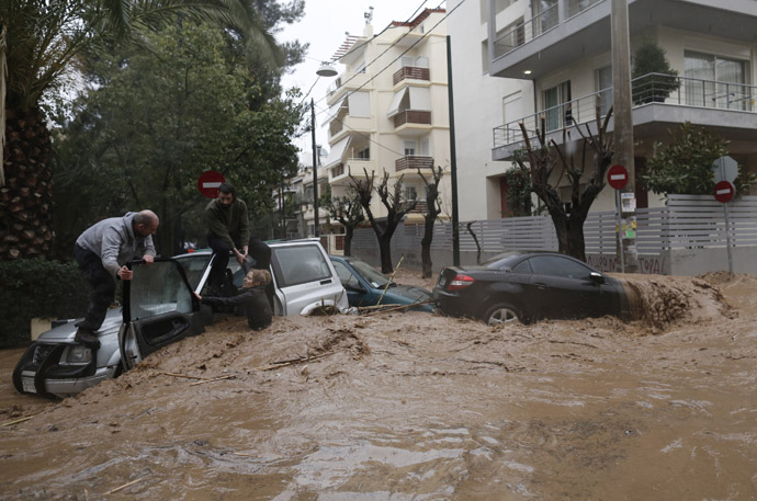 A woman is rescued from flood waters by a resident standing on top of her car during heavy rain in Chalandri suburb north of Athens February 22, 2013. (Reuters/John Kolesidis)