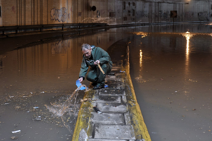 A municipality employee works at a flooded road in central Athens on February 22, 2013. (AFP Photo/Louisa Gouliamaki)