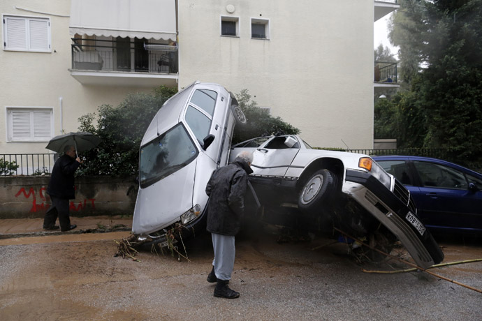 People look at damaged cars following heavy rain in Chalandri suburb north of Athens February 22, 2013. (Reuters/John Kolesidis)