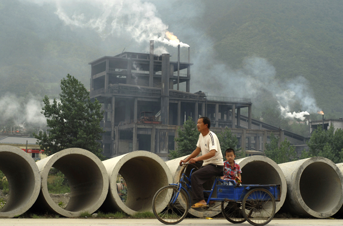 A man rides a tricycle with his son past a cement plant in Baokang. (Reuters)