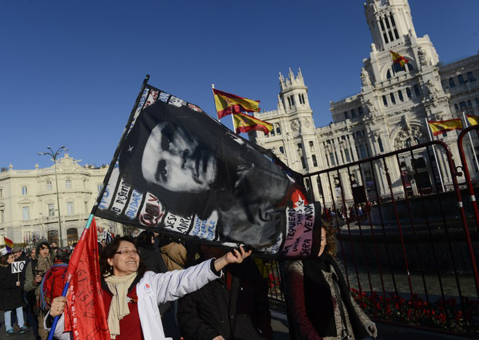 A woman holds a flag depicting a picture of Argentine-born Cuban revolution hero Che Guevara during a protest by public workers, small political parties and non-profit organisations against government austerity on February 23, 2013 in Madrid. (AFP Photo / Pierre-Pholippe Marcou)