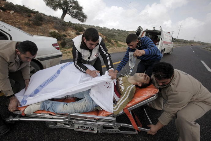 Palestinians paramedics aid a wounded protester following clashes with settlers in the West Bank village of Qusra near Nablus on February 23, 2013. (AFP Photo / Jaafar Ashtiyen)