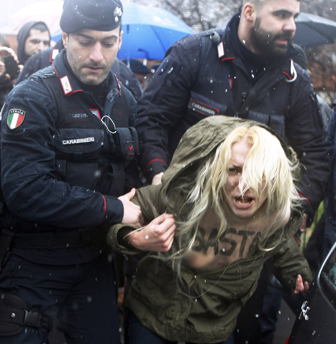 Carabinieri stop an activist from the women's rights organisation Femen during a protest outside the polling station where former Prime Minister Silvio Berlusconi cast his vote in Milan, February 24, 2013. (Reuters/Cezaro De Luca)