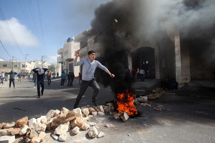 A Palestinian protester uses a slingshot to hurl stones towards Israeli security forces during clashes in the village of Saair, east the West Bank city of Hebron, on February 24, 2013. (AFP Photo / Hazem Bader)