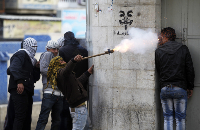 A Palestinian protester uses a makeshift launcher to shoot fire crackers as another protester takes cover during clashes with Israeli soldiers and border policemen in the West Bank city of Hebron February 24, 2013.(Reuters / Ammar Awad)