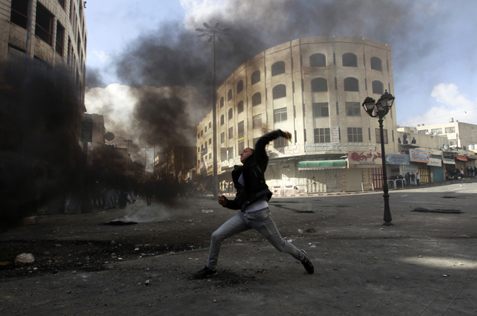 A Palestinian protester throws a stone during clashes with Israeli soldiers and border policemen in the West Bank city of Hebron February 24, 2013. (Reuters / Ammar Awad)