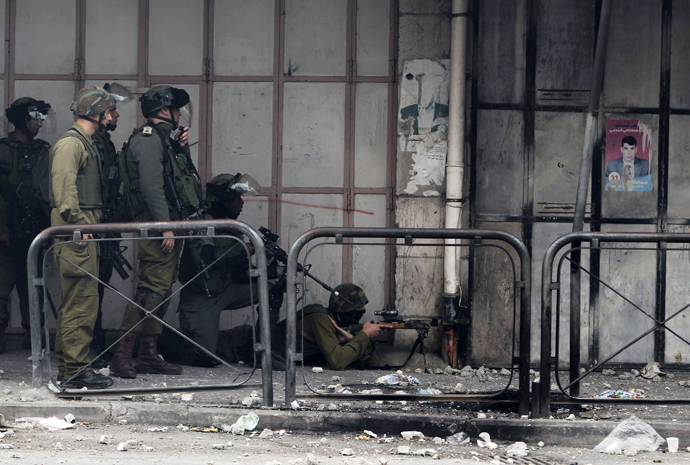 Israeli soldiers take position during clashes with stone-throwing Palestinian protesters in the West Bank city of Hebron February 24, 2013. (Reuters / Ammar Awad)