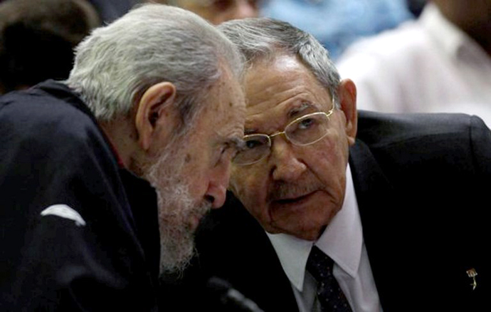Cuban leader and former president Fidel Castro (L) listening to his brother and current president, Raul, as Cuba's new National Assembly meets to choose a Council of State, at the Conventions Palace in Havana on February 24, 2013. (AFP Photo / Ismael Francisco)
