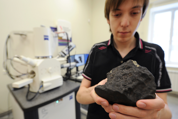 Grigory Yakovlev, engineer at the Research and Educational Center of Nanomaterials and Nanotechnologies of Ural Federal University, with fragment of the meteorite found during the expedition in the Chelyabinsk region. (RIA Novosti / Pavel Lysizin)
