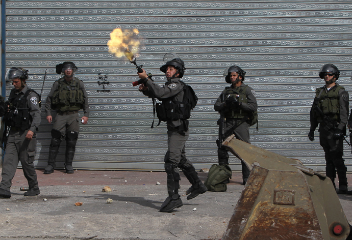 An Israeli border guard fires a tear gas cansiter during clashes with Palestinian youths outside Israel's Ofer prison near Ramallah on February 25, 2013. (AFP Photo / Abbas Momani)