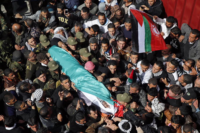 Palestinians carry the body of Arafat Jaradat as it arrives at his home before his funeral in the West Bank village of Se'eer near Hebron February 25, 2013. (Reuters / Darren Whiteside)