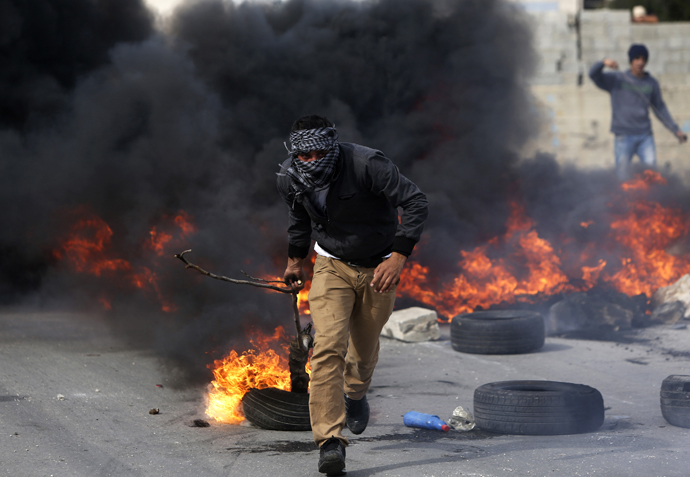 A stone-throwing Palestinian protester uses a branch to move a burning tyre during clashes with Israeli soldiers outside Israel's Ofer military prison near the West Bank city of Ramallah February 25, 2013. (Reuters / Mohamad Torokman)