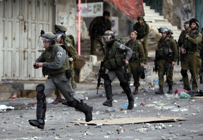 An Israeli border policeman holds a stun grenade as he runs during clashes with stone-throwing Palestinian protesters in the West Bank city of Hebron February 25, 2013. (Reuters / Ammar Awad)