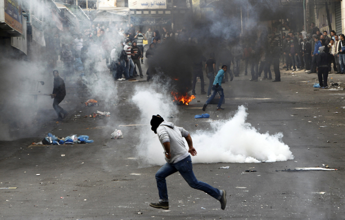 A stone-throwing Palestinian protester runs past tear gas fired by Israeli soldiers during clashes in the West Bank city of Hebron February 25, 2013. (Reuters / Ammar Awad)