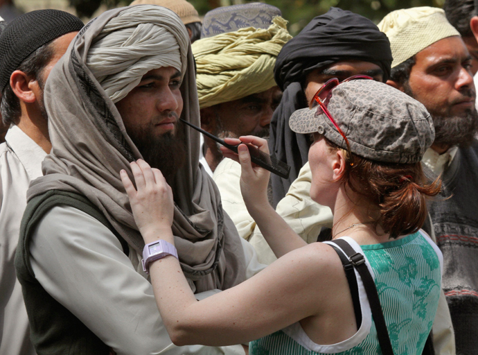 "A crew member of Oscar-winning director Kathryn Bigelow's team for the movie ""Zero Dark Thirty"" applies makeup on an actor during a shoot at the filming location in the northern Indian city of Chandigarh March 17, 2012 (Reuters / Ajay Verma)"