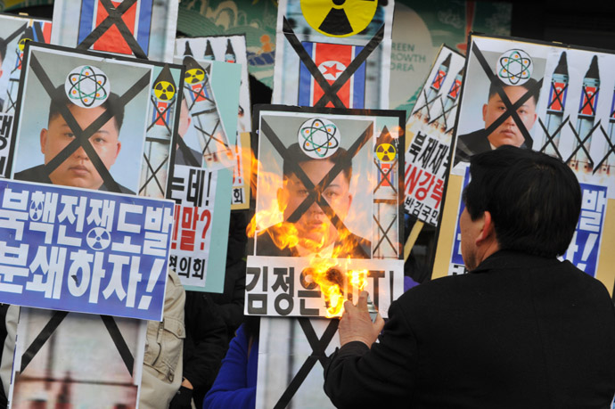 An activists from an anti-North Korea civic group burns a placard of North Korean leader Kim Jong Un during a protest agains North Korean nuclear test in Seoul on February 12, 2013. (AFP Photo/Kim Jae-Hwan)
