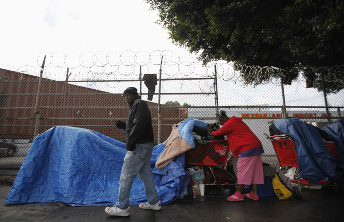 Homeless people protect their possessions from the rain across the street from where the Skid Row Housing Trust's 102 pre-fabricated 350 square foot modular apartments are put in place downtown, becoming the first housing complex of its type for the homeless in the nation, in Los Angeles, California, December 18, 2012. (Reuters/Lucy Nicholson)