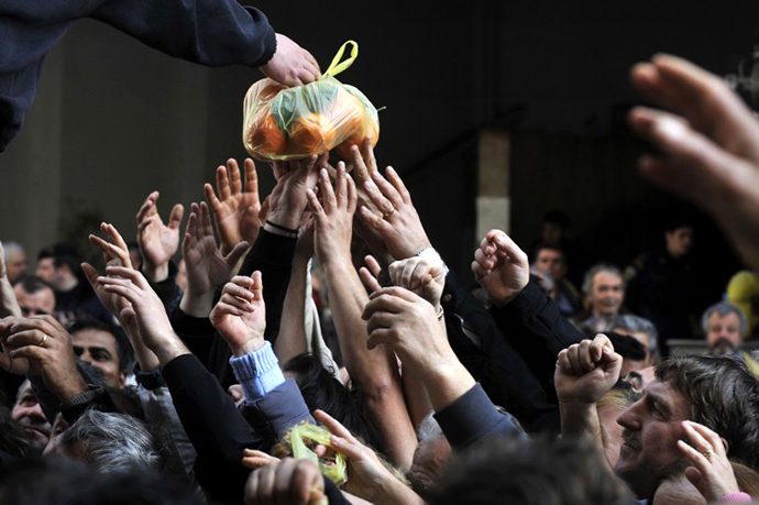 People reach out for a bag of oranges during a free distribution of fruit and vegetables by Greek farmers in Athens. (AFP Photo / Louisa Gouliamaki)