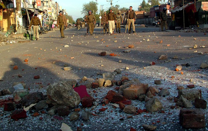 Indian police patrol along a street strewn with rocks after youth hurled stones at buses and police outside a hospital in a low-income area of New Delhi on March 1, 2013. (AFP Photo)