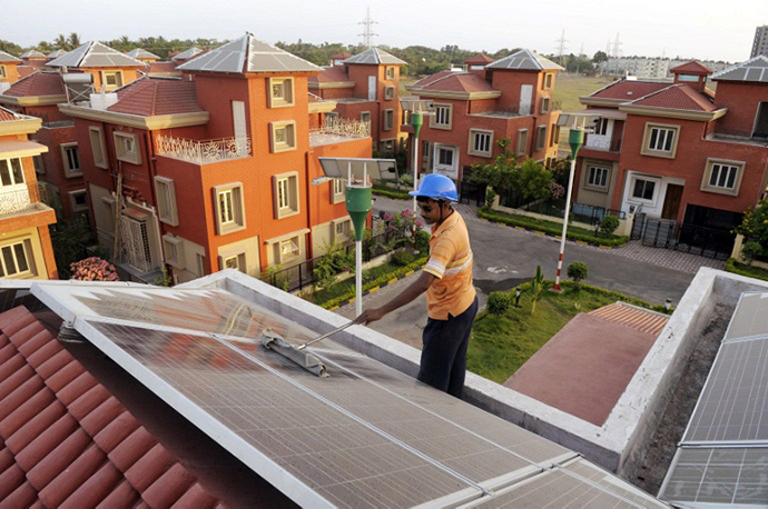 An Indian worker cleans solar panels fitted onto the roof of a residential house in Rabirashmi Abasan, a solar housing complex at Rajarhat close to Kolkata. (AFP Photo / Deshakalyan Chowdhury)