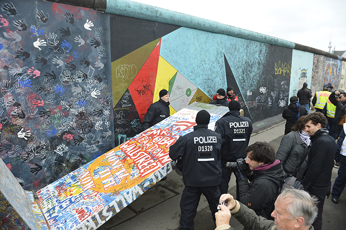 Police remove a piece of fake concrete used by protesters to fill out a whole during the removal of a section of the East Side Gallery, a 1,3 km long remainder of the Berlin Wall. (AFP Photo / Odd Andersen)